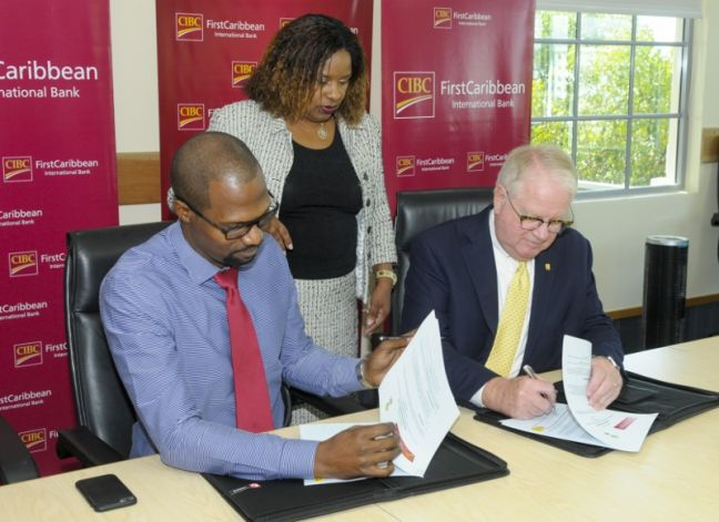 Gary Brown, CEO of CIBC FirstCaribbean International Barbados and Selwyn Cambridge, Founder of Ten Habitat, sign the agreement signifying the partnership between the two organisations. Witnessing the signing is Debra King, CIBC FirstCaribbean's Director of Corporate Communications and a Director of the bank's ComTrust Foundation. (Photo contributed)