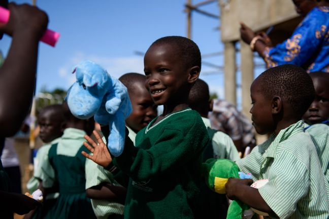A child attending school holds up a stuffed toy he received during a distribution of early childhood development kits and recreational kits from UNICEF in Yei, South Sudan. Photo: UNICEF/Hatcher-Moore