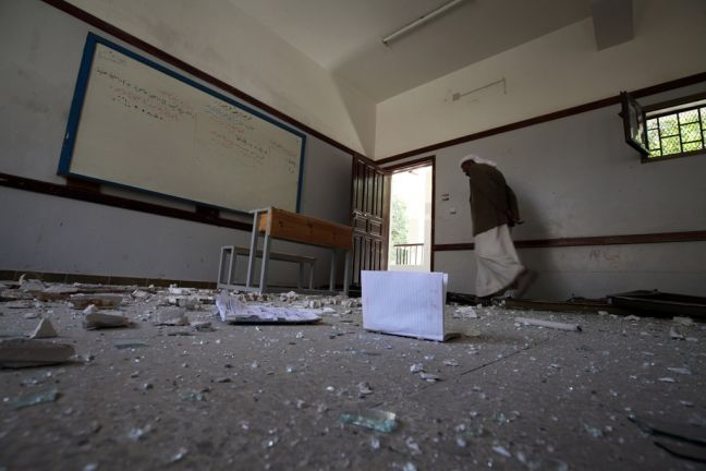 A school guard walks through a school in Yemen's capital Sana'a that was heavily damaged during an air strike on the building next to it. (File) Photo: UNICEF/Mahmoud