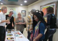 "Guests around the center table display of selected HNP books at the ""Art & Words"" exhibition. (SWC photo)"