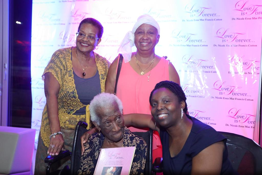VICMrs C holds book next to author Erna Mae Francis Cotton with her daughter Iona Carrington and neice Bernadine Van Veen standing INS3