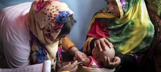 ©UNICEF/Brown A volunteer at the Primary Health Centre in on of Cox's Bazaar's vast refugee camps inoculates the baby of an 18-year-old mother, Bangladesh 2019.