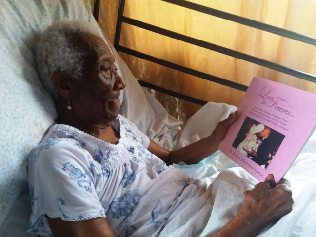 Centenarian Carmen Eleanore Hodge Carrington admiring her book, Love is Forever.