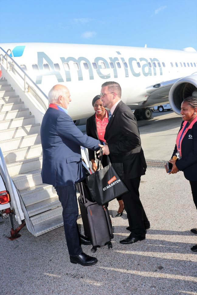Minister of Tourism, Economic Affairs, Transport & telecommunication (TEATT) the Honourable Stuart Johnson, greets Rotary International President Barry Rassin as he stepped off the American Airlines flight on Wednesday afternoon and presented him with a bag of welcome gifts from the St. Maarten Tourist Office.