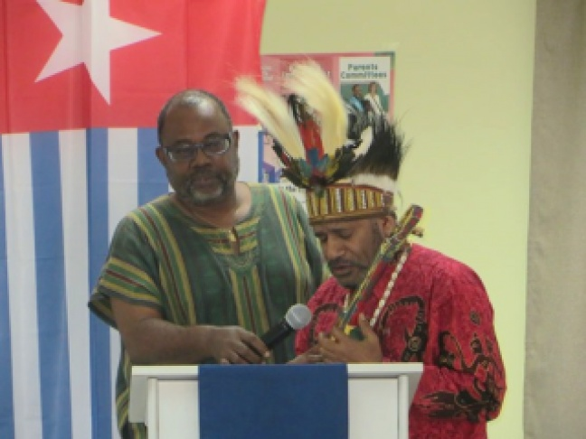 Brotherly solidarity at 12th annual St. Martin Book Fair as Dorbrene O'Marde (L), Antiguan author and member of the Caribbean Reparations Commission, assists Chief Benny Wenda, West Papua independence movement leader, with a Papuan freedom song at the book festival's Presidents' Forum (6.7.14)