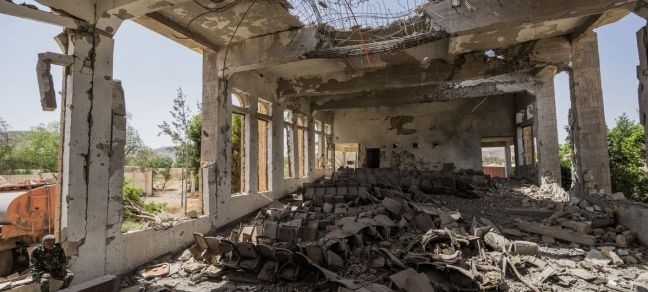 Giles Clarke/UN OCHA A military guard sits in the former Assembly Hall of the Governor of Saada. Since the Yemen conflict escalated in 2015, much of the city's infrastructure has been destroyed (file photo).