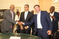 UTS shareholder representative, Mister of Justice, Cornelius De Weever shaking hands with Nicholas Collette at conclusion of signing. In center is Finance Minister Perry Geerlings and looking on are UTS CEO Paul de Geus and Finance Ministry staffers.