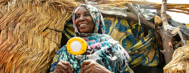 IOM/Jorge Gallindo. Hauwa's Gogla lamp helps her cook and carry out other chores around her home, and it helps her children study.