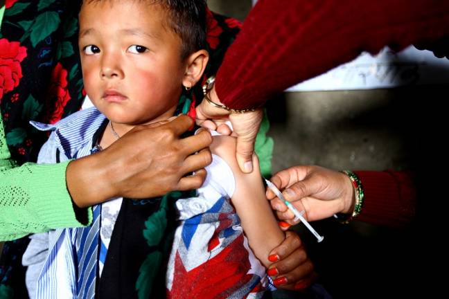 A young boy is administered measles and rubella vaccine at a health post in Gorkha District, Nepal. Photo: UNICEF/Kiran Panday