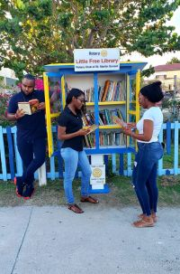 Guests of Rotary Sunset, Gabriel, Tivona and Shanyca exploring the books at the launch of the club's newly installed Little Free Library in Simpson Bay.