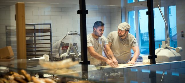 © UNHCR/Gordon Welters Syrian refugee Mohamad Hamza Alemam (left) is receiving baking lessons from Master baker Björn Wiese (wearing cap), at the Backwerkstatt Bakery in Eberswalde, eastern Germany. 4 December 2018.