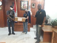 On the left, two law enforcement officials are holding a box containing PPEs that were just presented by Leslie Richardson (r), Safety and Security Manager of Port St. Maarten.