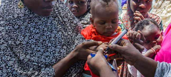 UNICEF/Andrew Esiebo UNICEF health worker uses a pen to mark the thumb of Ajeda Mallam, 6 months, who has just been vaccinated against polio at a camp for internally displaced persons outside Maiduguri northeast Nigeria. Photo: UNICEF/Andrew Esiebo