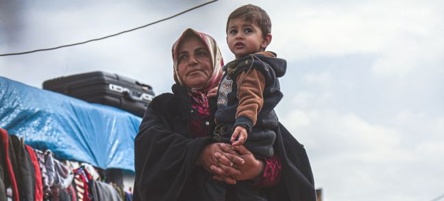 OCHA/Steve Hafez A widow holds her grandson in a displaced persons camp in northern Idleb Governorate, Syria.