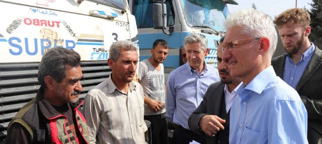 OCHA/David Swanson The UN Humanitarian Coordinator, Mark Lowcock (r), meets with a group of Syrian drivers on the Turkish side of the two countries' common border (file photo).