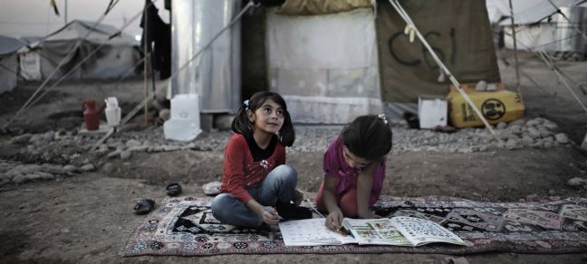 UNICEF/Romenzi Seated on a rug atop the dirt ground, two girls complete homework outside their tent home, in the Kawergosk camp for Syrian refugees, west of Erbil, Iraq.