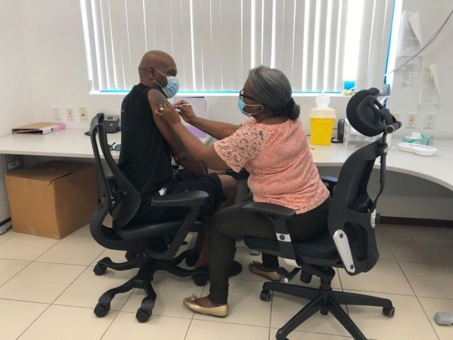 A member of the CPS Vaccination Team inoculating a person who had registered for their COVID-19 vaccine.