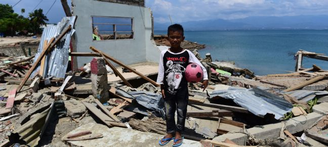 UNICEF/UN0240792/Wilander Rido Saputra, 10 years old, stands in front of his home which was destroyed by the tsunami in Donggala Regency, Central Sulawesi, Indonesia (3 October).