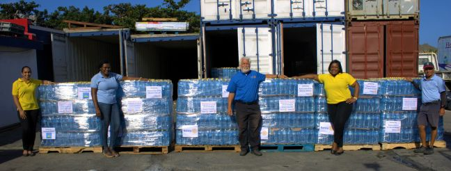 L to R: Rotarian Franjesca Bulbaai, District Governor Elect Louis Wever, President Grace Linger, President Elisia Lake, and Heavenly Water Representative posed with 6 of the 12 pallets of water before being shipped to St. Vincent.